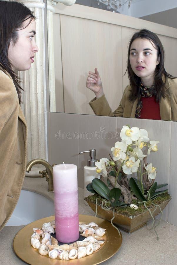 Mulher na frente de um espelho foto de stock royalty free