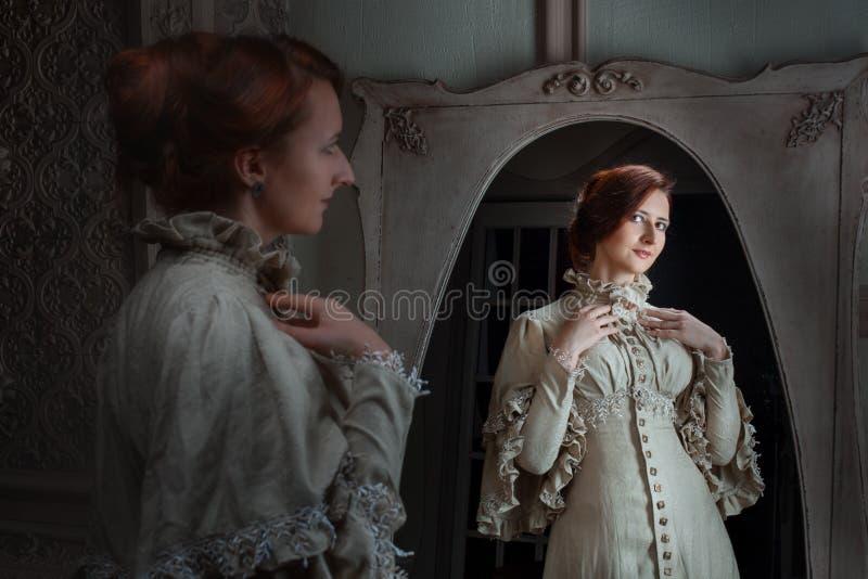 A mulher na frente de um espelho faz o toalete fotografia de stock royalty free