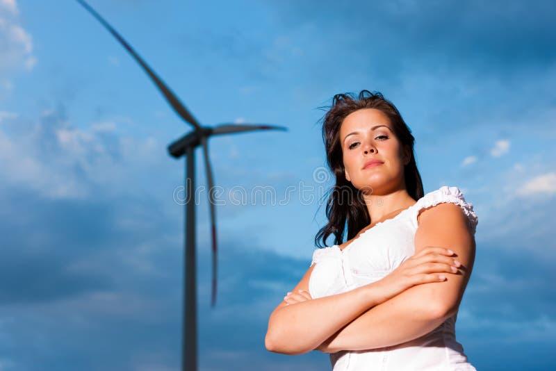 Mulher na frente do moinho de vento e do céu imagem de stock royalty free