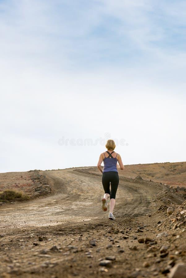 Mulher na fuga da sujeira que faz a corrida da aptidão fotografia de stock