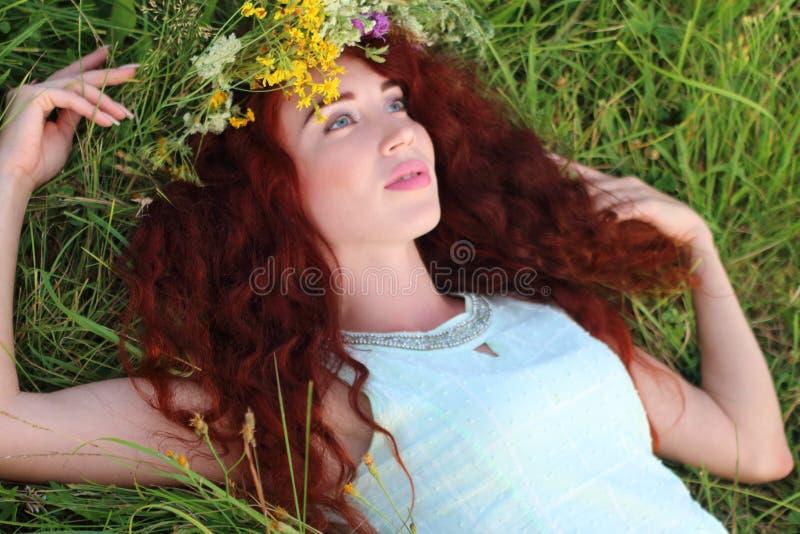 A mulher na grinalda encontra-se na grama e olha-se acima no prado na SU fotografia de stock royalty free