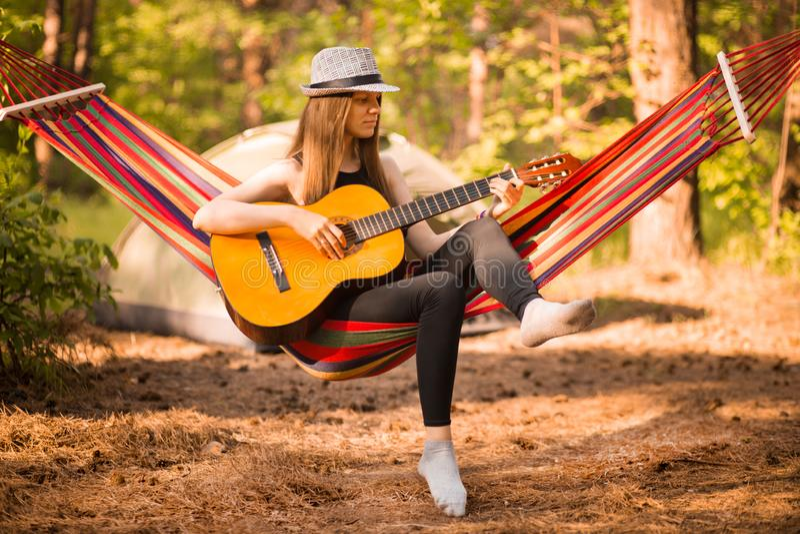 Mulher na guitarra do jogo do chap?u e relaxamento na rede que pendura entre pinheiros no fundo imagens de stock
