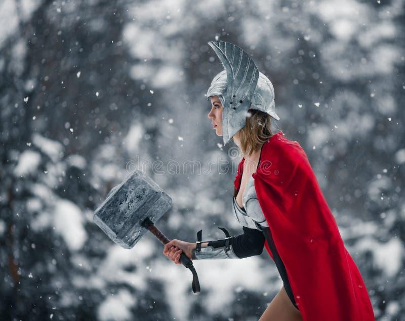 A mulher na imagem do deus de trovão Germânico-escandinavo e de tempestade vai com o martelo em sua mão Cosplay fotografia de stock royalty free