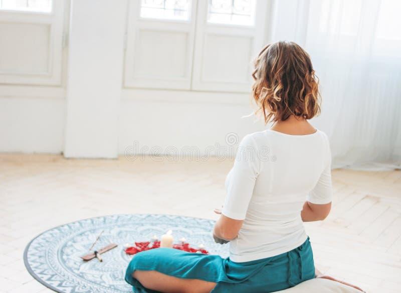 Mulher na ioga praticando do traje étnico na frente das velas e das pétalas cor-de-rosa vermelhas, vista da parte traseira fotos de stock