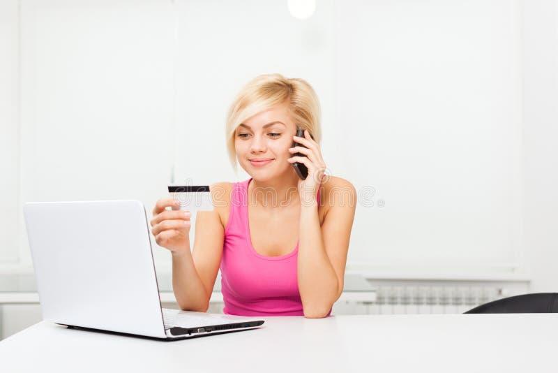 Mulher na linha portátil do cartão de crédito da compra fotografia de stock