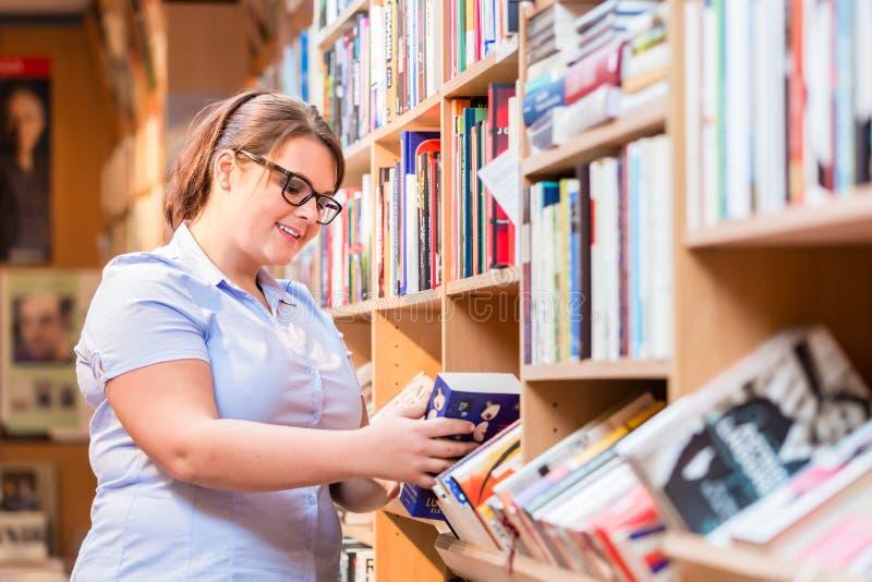 Mulher na livraria que procura o livro fotografia de stock