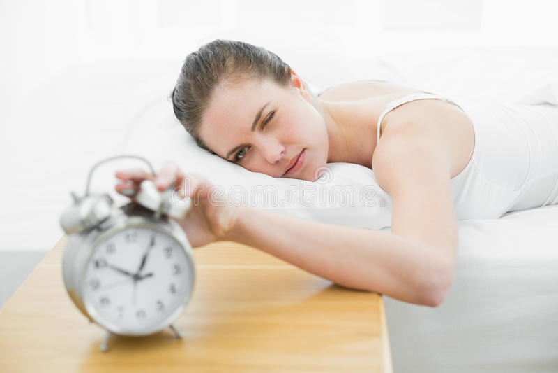 Mulher na mão de alargamento da cama ao despertador foto de stock