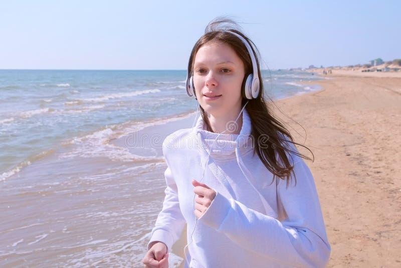 Mulher na música dos fones de ouvido que movimenta-se no treinamento exterior da corrida do esporte da praia da areia do mar foto de stock royalty free