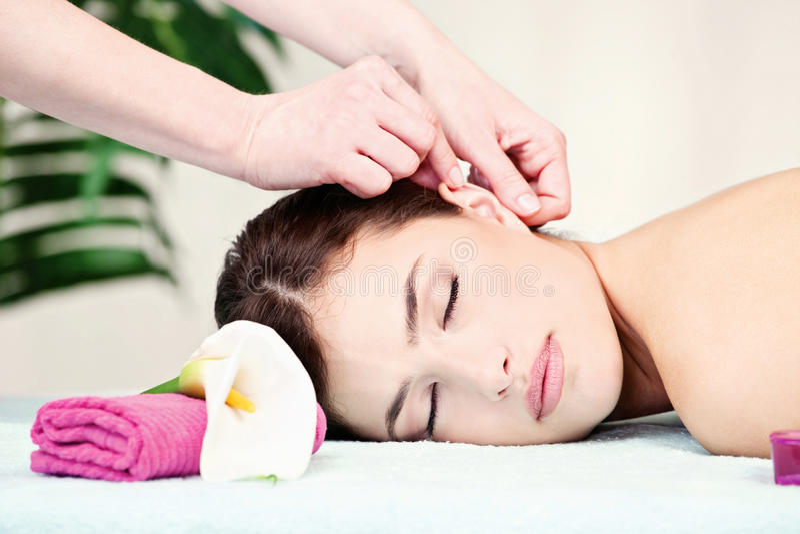Mulher na massagem da orelha no salão de beleza fotografia de stock royalty free