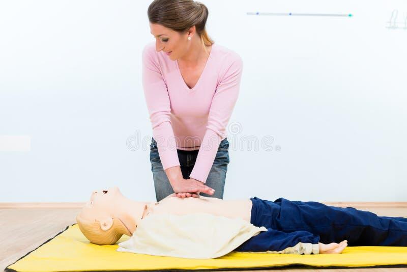 Mulher na massagem de coração praticando do curso dos primeiros socorros fotografia de stock royalty free