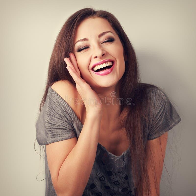 Mulher na moda de riso da composição com a boca largamente aberta e o olho fechado foto de stock