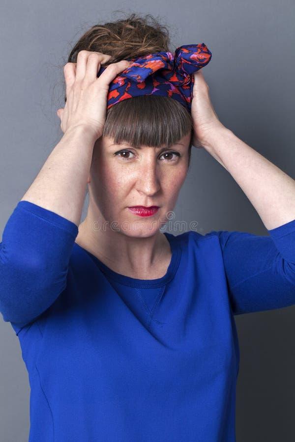 Mulher na moda mal-humorada que ajusta seu lenço para o penteado elegante imagens de stock royalty free
