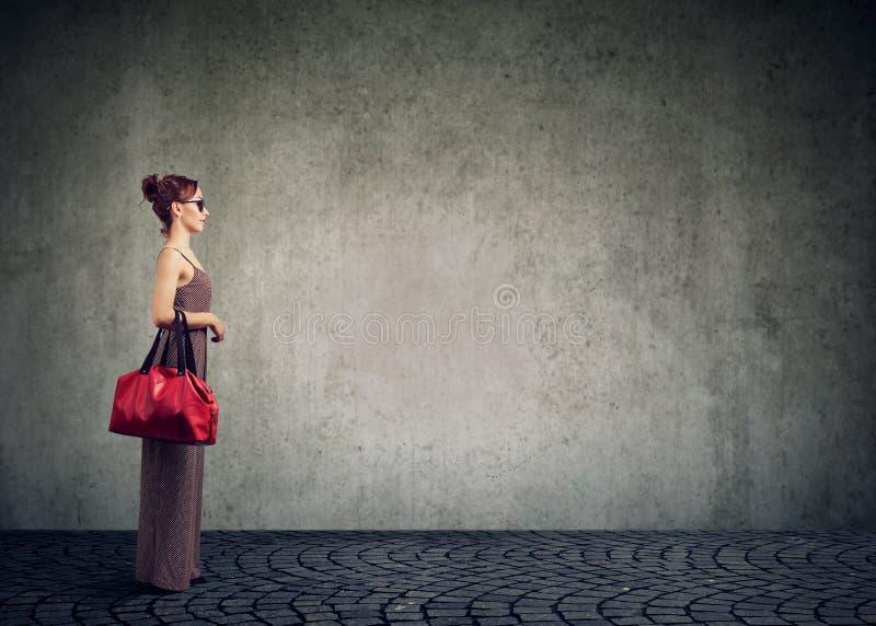 Mulher na moda moderna nos óculos de sol e posição do vestido com o saco no fundo cinzento imagens de stock