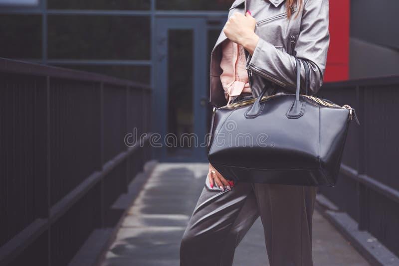 Mulher na moda no revestimento das calças da prata com olhar preto da rua do saco à disposição Equipamento elegante foto de stock