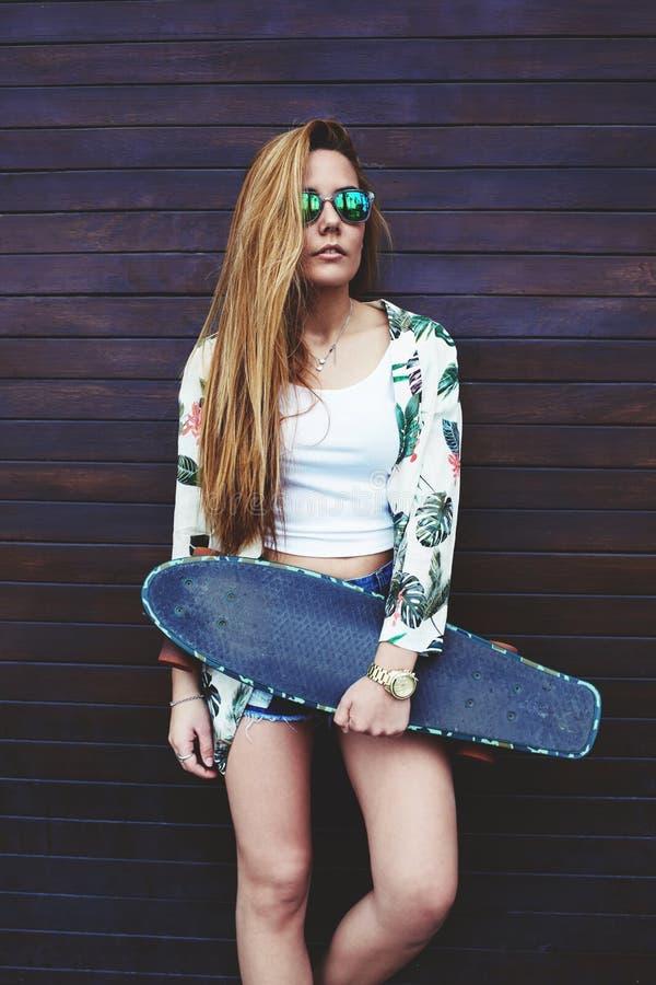 Mulher na moda nova nos óculos de sol que levantam com seu longboard que aprecia o bom dia no verão imagens de stock royalty free