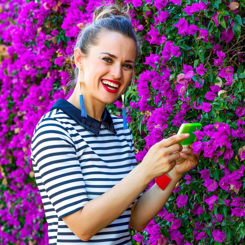 Mulher na moda perto da cama de flores que toma a foto com smartphone foto de stock