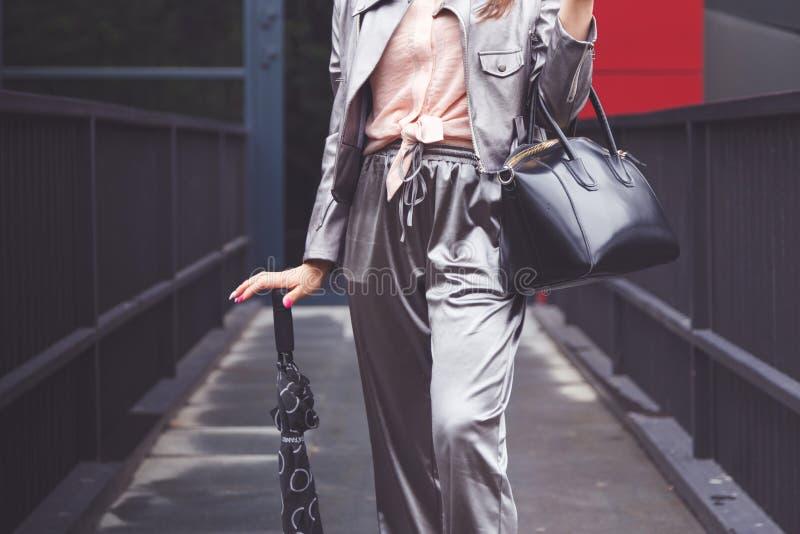 A mulher na moda na prata arfa o revestimento com a bolsa e o guarda-chuva de couro pretos Equipamento elegante fotos de stock royalty free
