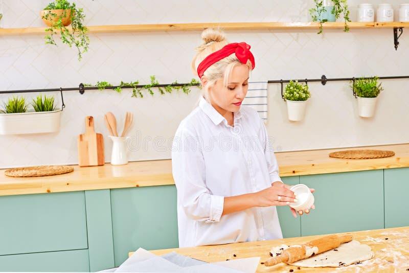 Mulher na moda que prepara a pastelaria na mesa de cozinha fotografia de stock
