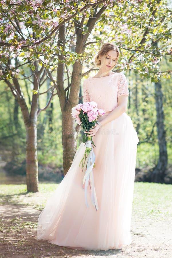Mulher na mola no parque fundo da flor de sakura com o ramalhete das peônias imagens de stock royalty free