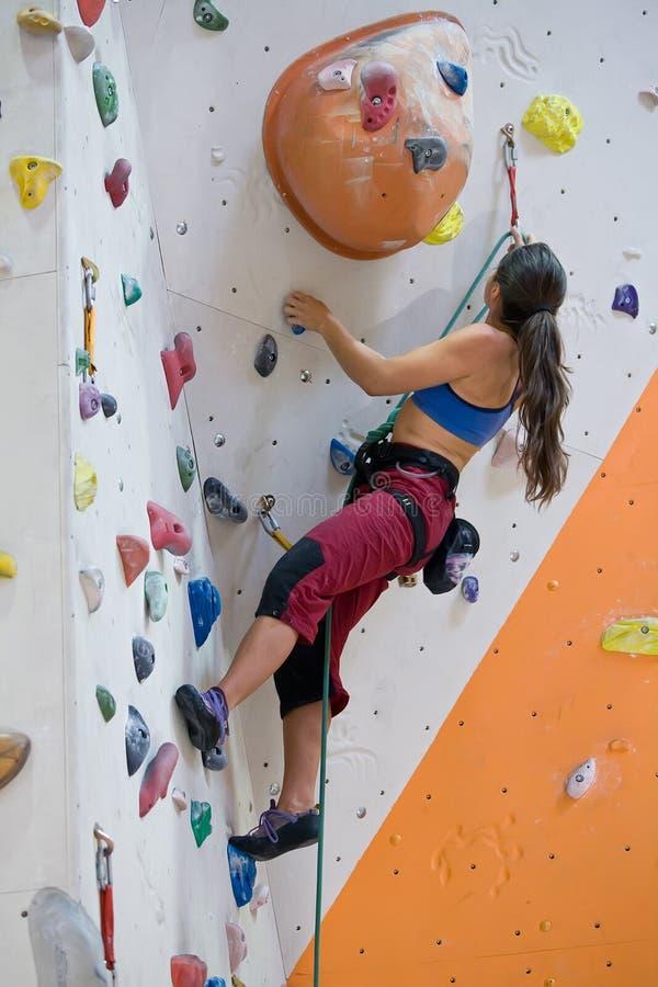 Mulher na parede de escalada imagem de stock