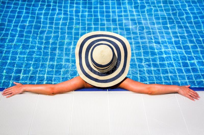Mulher na piscina de relaxamento do chapéu de palha fotografia de stock royalty free