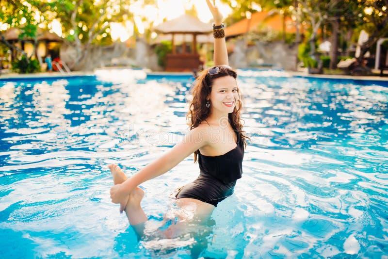 Mulher na piscina em férias de verão verão, menina 'sexy' com estilo de vida luxuoso na forma do biquini Menina que tem o fu imagens de stock
