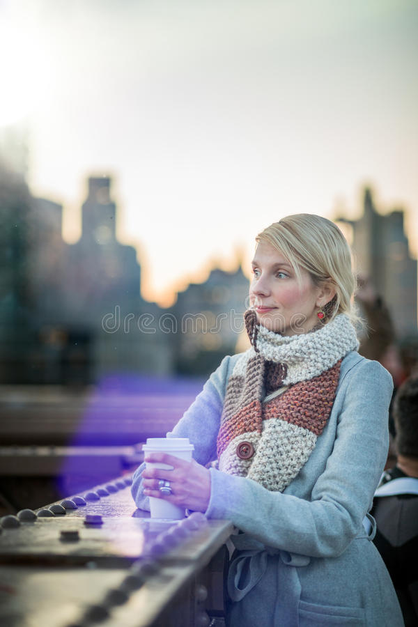 Mulher na ponte de Brooklyn que olha Manhattan com um café foto de stock royalty free