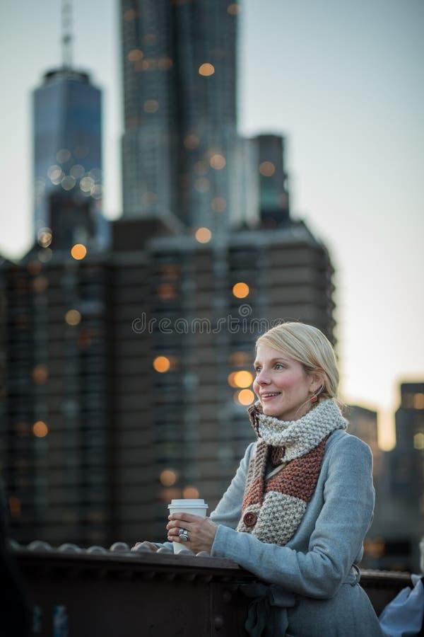Mulher na ponte de Brooklyn que olha Manhattan com um café fotos de stock