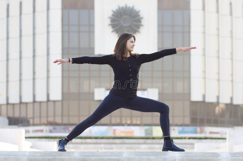 Mulher na pose da ioga na cidade imagem de stock