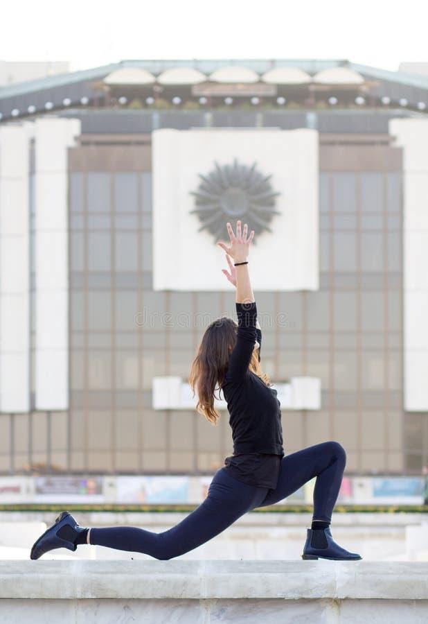 Mulher na pose da ioga na cidade fotografia de stock royalty free