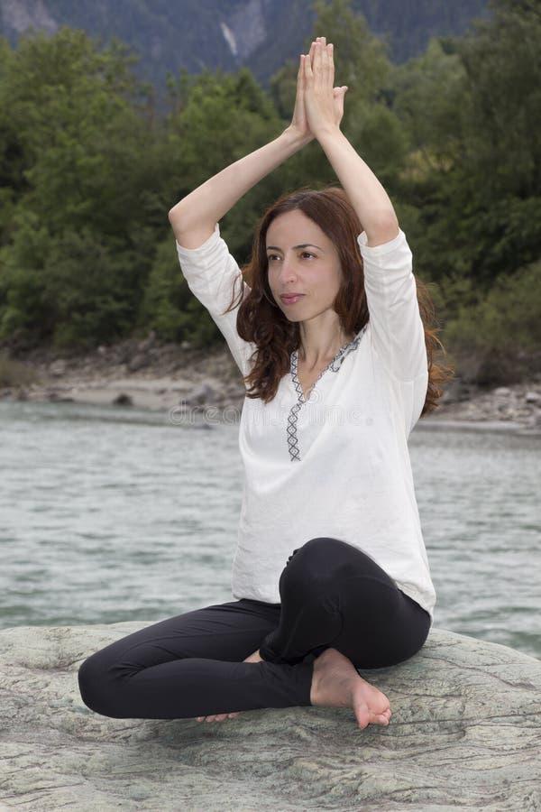 Mulher na pose de Namaste fora por um rio fotografia de stock royalty free