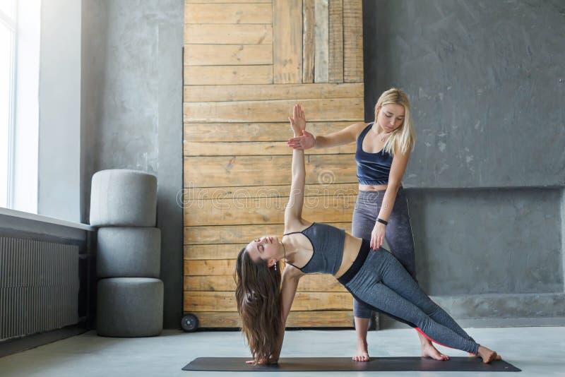 Mulher na pose lateral da prancha com o instrutor na classe da ioga fotografia de stock
