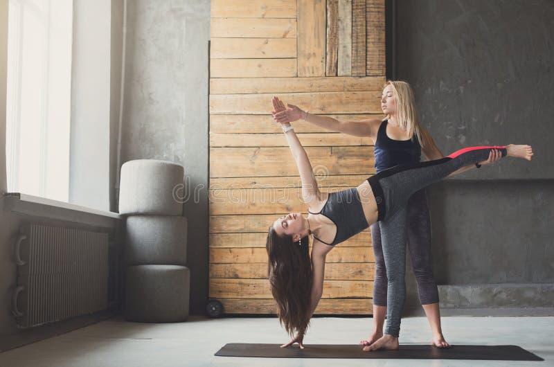 Mulher na pose lateral da prancha com o instrutor na classe da ioga foto de stock royalty free