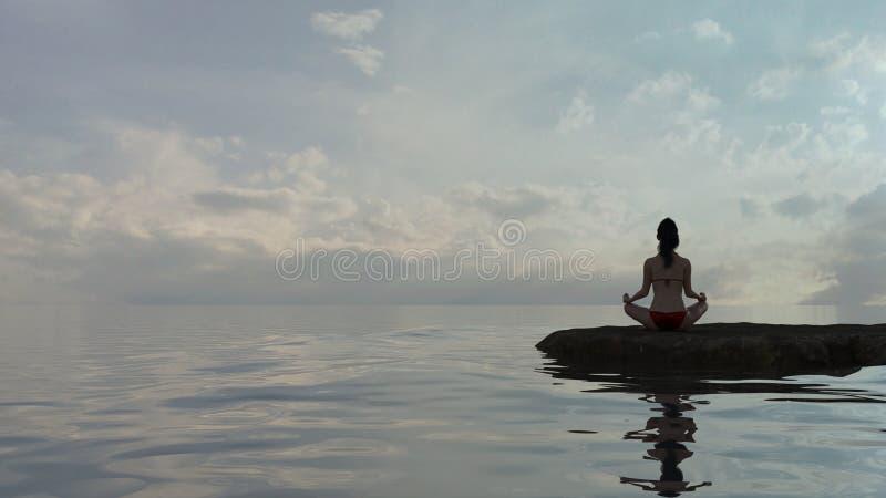 Mulher na posição de lótus da ioga pela água no crepúsculo fotografia de stock