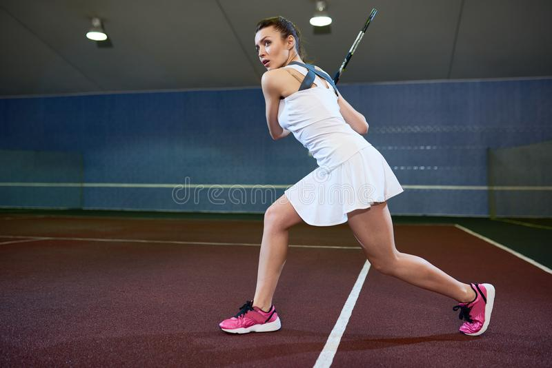 Mulher na prática resistente do tênis foto de stock