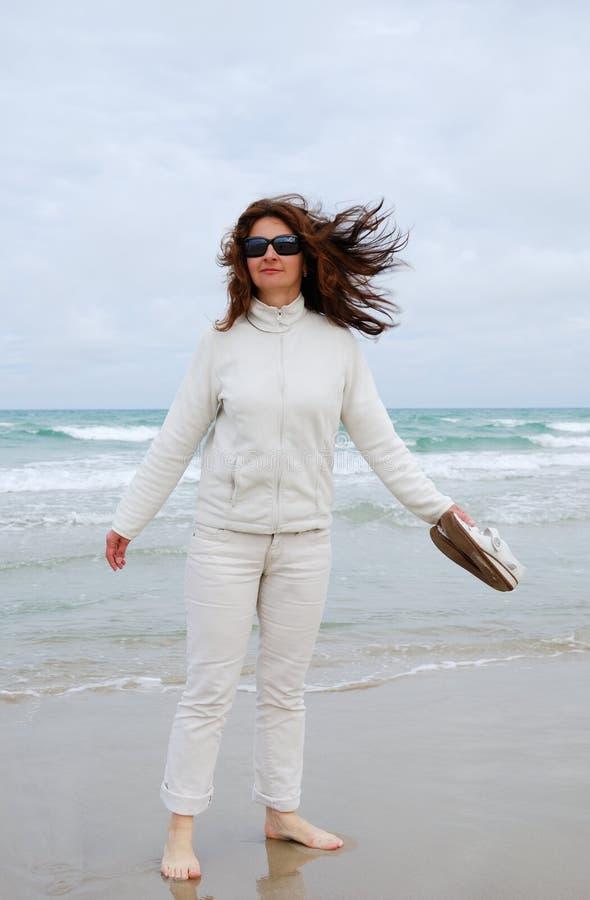 Mulher na praia de encontro ao céu nebuloso. foto de stock royalty free