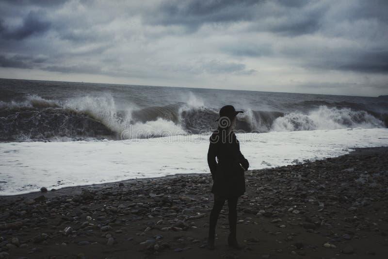 Mulher na praia durante uma tempestade foto de stock