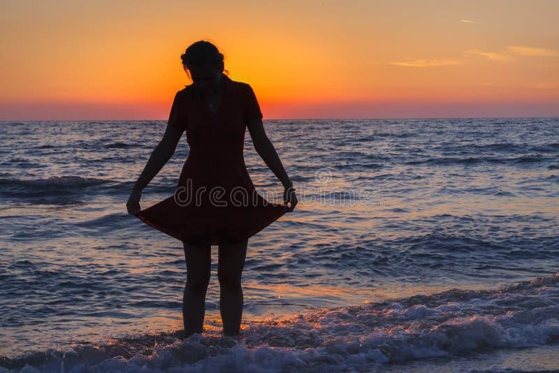 Mulher na praia que aprecia o por do sol bonito foto de stock royalty free