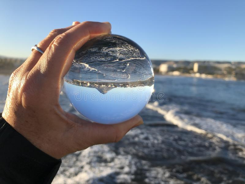 Mulher na praia que guarda uma bola de cristal fotografia de stock royalty free