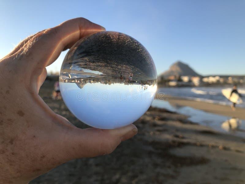 Mulher na praia que guarda uma bola de cristal imagens de stock royalty free