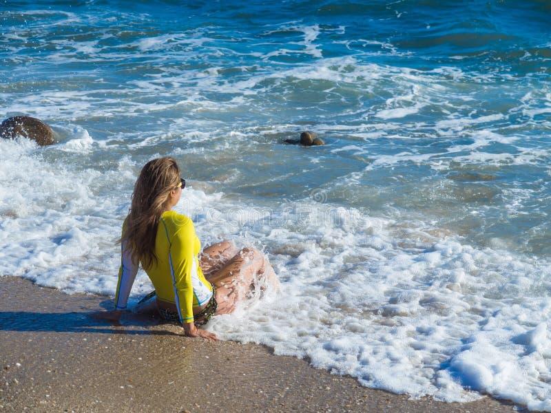 Mulher na praia rochosa imagens de stock royalty free