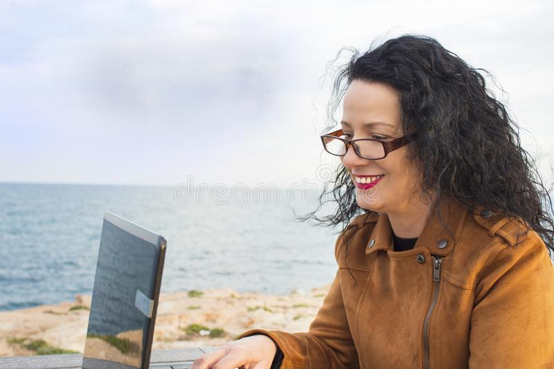 Mulher na praia Sorriso e jovem mulher feliz contra o mar com um computador fotos de stock