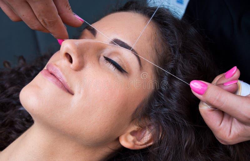 Mulher na remoção dos pêlos faciais que rosqueia o procedimento fotografia de stock