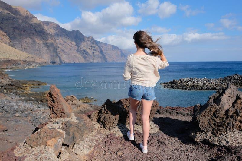 Mulher na rocha vulcânica que olha o mar e os penhascos fotos de stock