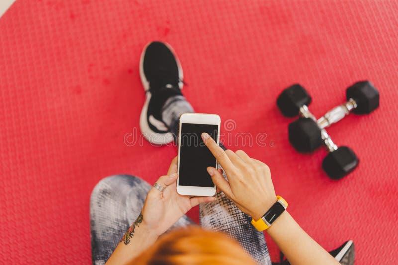 Mulher na roupa da aptidão usando o smartphone no gym para o exercício imagens de stock