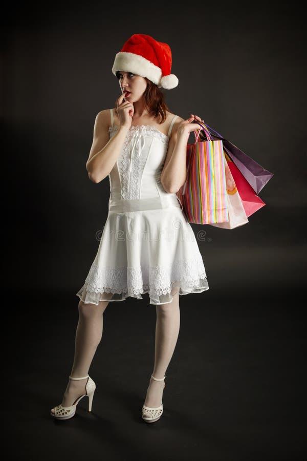 A mulher na roupa de ano novo pensa da compra imagens de stock
