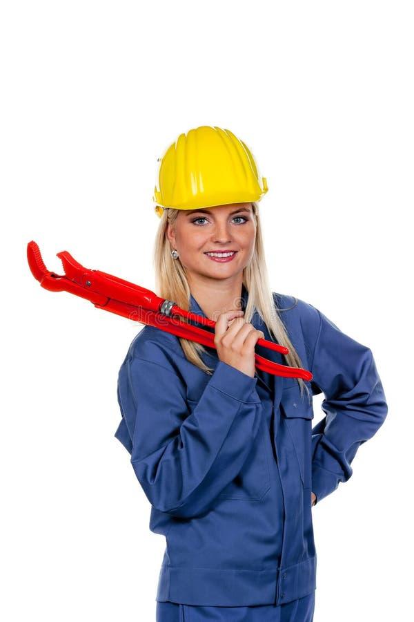 Mulher na roupa de trabalho azul com chave de tubulação imagem de stock