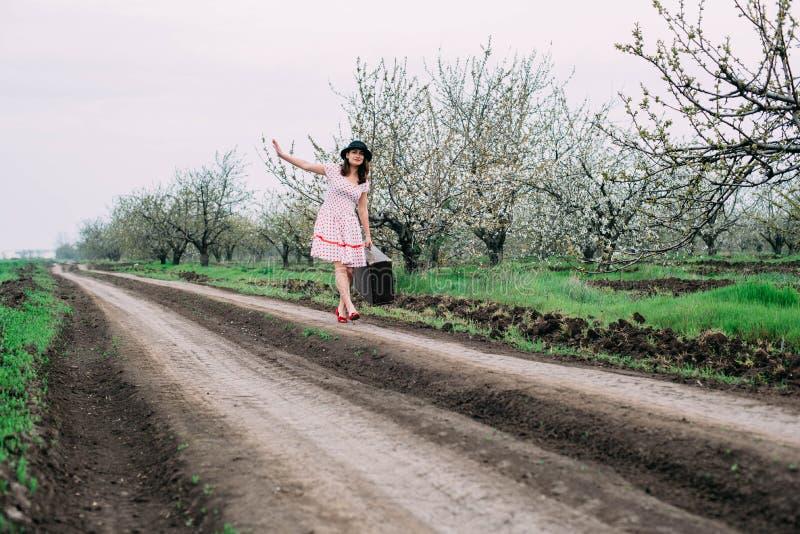 Mulher na roupa do vintage com mala de viagem foto de stock royalty free