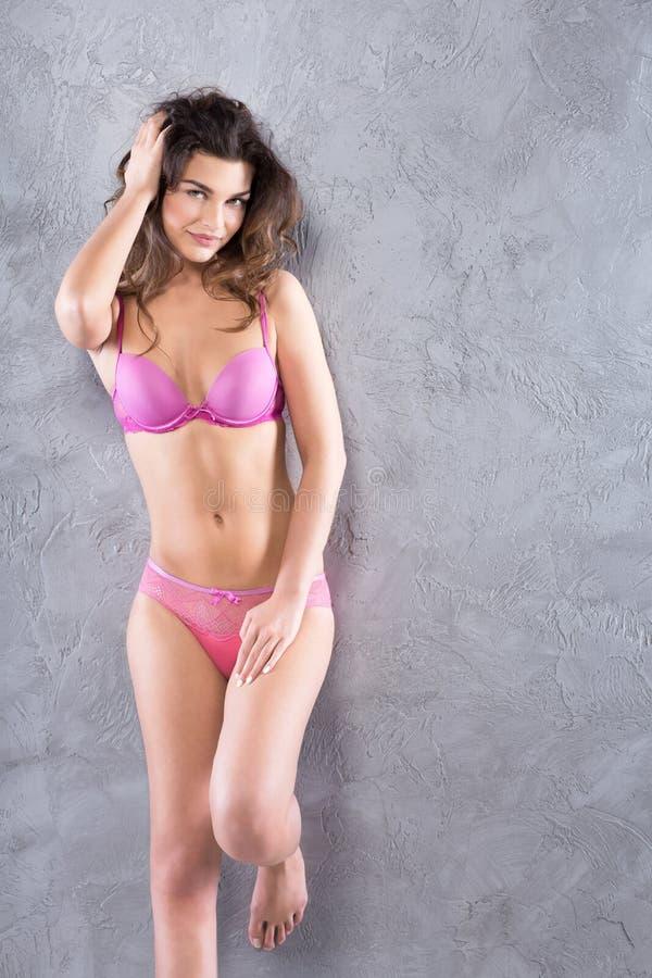 Mulher na roupa interior cor-de-rosa fotografia de stock