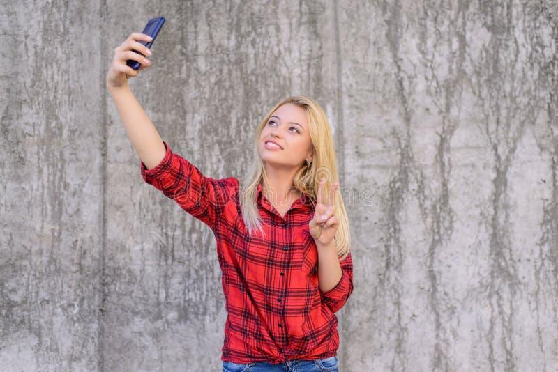 Mulher na roupa ocasional com selfie taling do sorriso de irradiação em seu smartphone e mostrar a telefone celular da pilha do v foto de stock royalty free